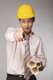 Young caucasian engineer with plans pointing finger at you Royalty Free Stock Image