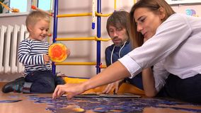 Young caucasian family assembling puzzle and reading book together. Man, woman and cute little boy having free time at stock footage