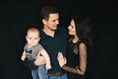 Young Caucasian family on a black background. Happy dad, mom and son. Loving couple holding a child. Young Caucasian family on a black background in the Studio stock image