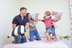 Young Caucasian Family Having a Playful Funny Pillow Fight Indoors Royalty Free Stock Photo