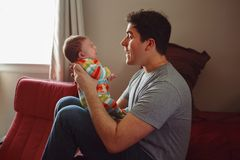 Young Caucasian father playing with newborn baby. stock photos