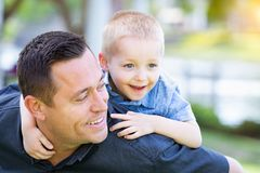 Playful Caucasian Father and Son Having Fun At The Park. Young Caucasian Father and Son Having Fun At The Park Stock Images