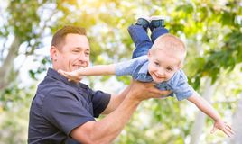 Young Caucasian Father and Son Having Fun At The Park. Young Caucasian Father and Son Having Fun Playing At The Park Stock Photography