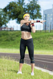 Young Caucasian Female in Athletic Sportgear Having Stretching Excercises Outdoors. Royalty Free Stock Images