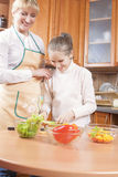 Young Caucasian Female Blond Teaching Her Daughter to Cook Royalty Free Stock Photo