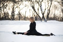 Young caucasian female blonde in leggings stretching exercise sitting on a string at open air in snowy forest. fit and sports royalty free stock photo