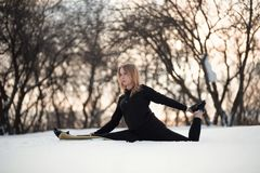 Young caucasian female blonde in leggings stretching exercise sitting on a string at open air in snowy forest. fit and sports stock photo