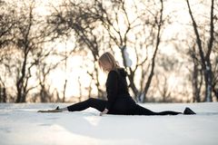 Young caucasian female blonde in leggings stretching exercise sitting on a string at open air in snowy forest. fit and sports stock images