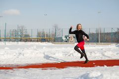 Young caucasian female blonde in red leggings stretching exercise on a red running track in a snowy stadium. fit and sports royalty free stock photo