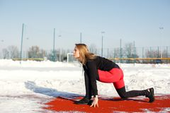 Young caucasian female blonde in red leggings stretching exercise on a red running track in a snowy stadium. fit and sports stock image