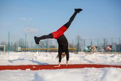 Young caucasian female blonde in red leggings stretching exercise on a red running track in a snowy stadium. fit and sports royalty free stock photography