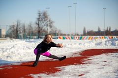 Young caucasian female blonde in violet leggings stretching exercise on a red running track in a snowy stadium. fit and sports royalty free stock photography