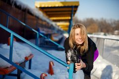 Young caucasian female blonde in violet leggings stretching exercise on tribune on a snowy stadium. fit and sports lifestyle royalty free stock photo