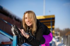 Young caucasian female blonde in violet leggings stretching exercise on tribune on a snowy stadium. fit and sports lifestyle stock photos