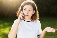 Young Caucasian female chatting with her friends over mobile phone having confused expression, raising her hands while being emoti stock photos