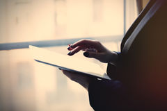Young caucasian female hands holding a tablet and typing text ne. Ar the window royalty free stock photography