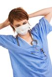 Young Caucasian female medical assistant. Young adult Caucasian female medical assistant dressed in scrubs putting on a protective mask Royalty Free Stock Photo