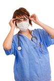 Young Caucasian female medical doctor. Young adult Caucasian female medical doctor dressed in scrubs putting on protective wear Stock Photography