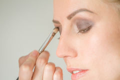 Young caucasian female model at a makeup. Applying make up to a. Young beautiful model royalty free stock photos