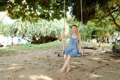 Young caucasian female person wearing jeans dress and riding on swing, sand in background. stock photo