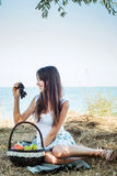 Young caucasian female on seaside with basket with fruits Royalty Free Stock Photo