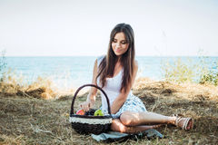 Young caucasian female on seaside with basket with fruits. Girl Royalty Free Stock Photo