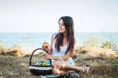 Young caucasian female on seaside with basket with fruits Royalty Free Stock Photography