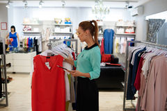 Young Caucasian female shop manager using digital tablet for examines products in interior of female clothing boutique Royalty Free Stock Images