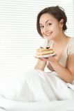 Young Caucasian female sitting in bed with a cake Royalty Free Stock Photography