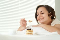 Young Caucasian female sitting in bed with a cake Royalty Free Stock Photos