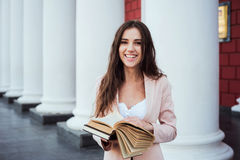 Young caucasian female student with books on campus. Student study in campus area Royalty Free Stock Images