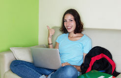 Young caucasian female student with computer showing thumb up Stock Image