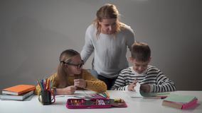 Young Caucasian female teacher giving task to children. Pretty girl in eyeglasses and her male classmate sitting at the stock video footage