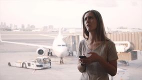 Young Caucasian female traveler uses smartphone, gets frustrated after listening to announcement near airport window. Young Caucasian female traveler standing stock video footage