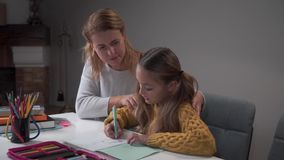 Young Caucasian female tutor teaching cute little girl at home. Smart schoolchild writing in the exercise book, teacher stock video footage