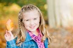 Young Caucasian Girl with Autumn Leaf royalty free stock images