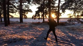 A young caucasian girl with backpack going on winter forest road in snow covered winter pine forest at sunset. Walk
