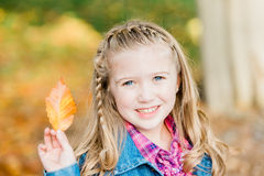 Young Caucasian Girl with Braided Hair Holding Leaf stock photo