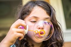 Young caucasian girl child blowing soap bubbles. Close up of young caucasian girl child blowing soap bubbles. Horizontal composition stock photo