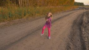 Young caucasian girl dancing hip-hop on country road. White blonde long hair girl singing outdoors. Staying in field rural scene autumn sunset. Handheld full stock footage