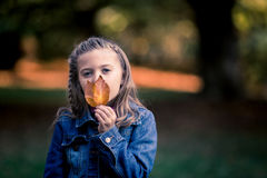 Young Caucasian Girl in Denim Jacket Holding Leaf stock photos