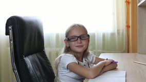 Young caucasian girl in glasses sitting on chair by table. Indoors close up view on pretty girl in glasses. White stock video footage