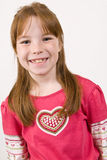 Young Caucasian girl in a heart shirt and smiling. A young Caucasian girl in a heart shirt, facing forward and smiling Royalty Free Stock Images