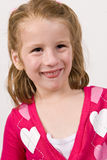 Young girl in a heart sweater making funny face Royalty Free Stock Photography