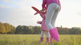 Young caucasian girl helping her little cute sister playing with a pink toy airplane. Pretty blonde child in dotted. Jacket running in the autumn evening stock video