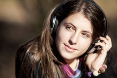 Young caucasian girl listening to music. With headphones looking aside stock image