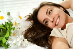 Young Caucasian girl lying in bed with flowers Stock Photos