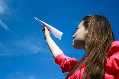 Young caucasian girl with paper plane in the hand Stock Photography