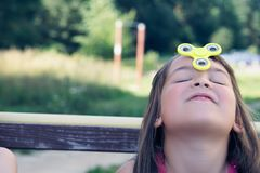 Young caucasian girl play with fidget spinner stress relieving toy on her forehead. Happy smiling child playing with Spinner stock images