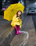 Young caucasian girl playing in the rain. Young caucasian girl with brown hair playing in the rain with yellow umbrella and raincoat with pink rainboots Royalty Free Stock Photos